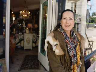 Middle-aged woman standing in front of antique shop