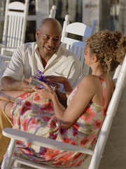 Middle-aged African American couple exchanging gifts outdoors