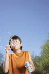 Hispanic boy blowing bubbles outdoors