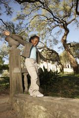 African American girl balancing on wall