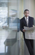 Businessman with newspaper leaning on glass wall