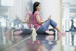Young woman sitting on reflective floor with mp3 player