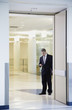 Businessman with mp3 player in doorway