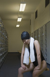 Female Asian swimmer with towel in locker room