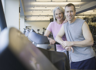 Couple standing on treadmill at gym