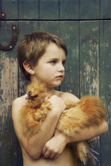 Boy leaning against barn holding chicken