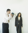 Businessman with megaphone yelling at businesswoman