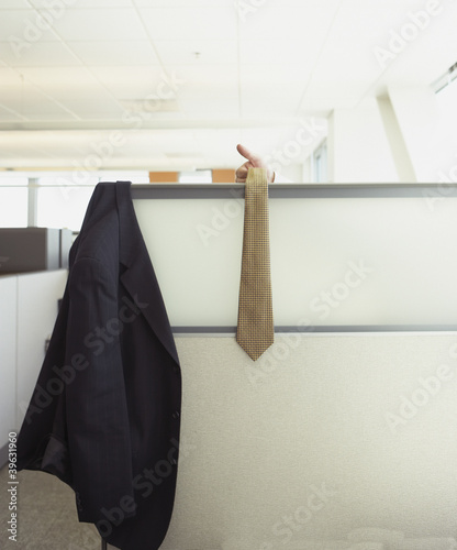 Suit jacket and tie hanging over cubicle wall