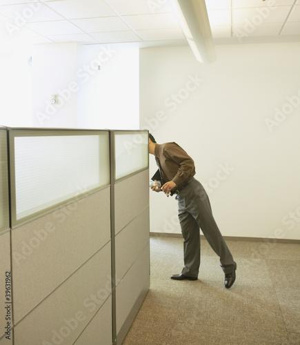 Businessman peeking around cubicle wall