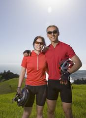 Asian couple wearing bicycle gear in countryside