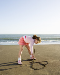 Girl drawing a heart in the sand