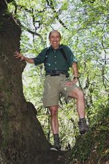 Senior Hispanic man standing in tree