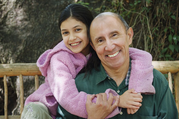 Hispanic grandfather and granddaughter hugging outdoors