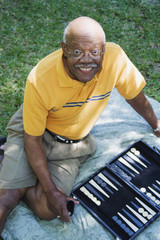 Senior African man playing backgammon outdoors