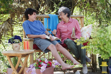 Hispanic grandmother and grandson reading outdoors