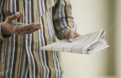 Close up of African man with pen and newspaper
