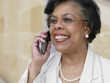 Senior African businesswoman using cell phone outdoors
