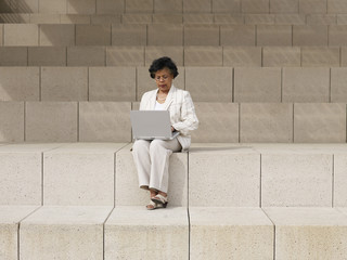 Senior African businesswoman using laptop on steps outdoors