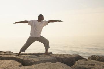 African man doing yoga on rocks at beach