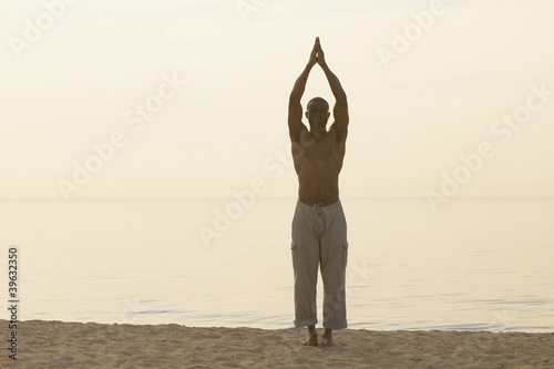 African man doing yoga at beach