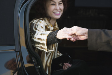 Asian woman being helped out of luxury car