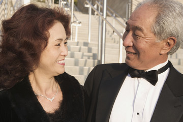 Senior Asian couple in evening wear outdoors