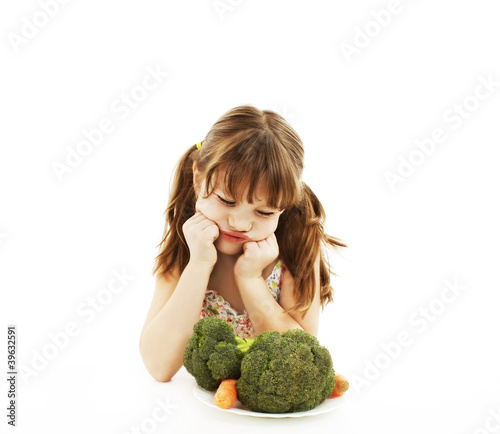 A cute little girl looks in disgust at her plate of vegetables