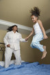 African mother and daughter jumping on bed