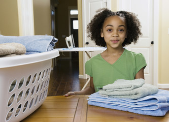 African girl with folded laundry