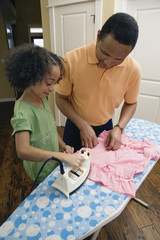 African father and daughter ironing