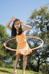 Hispanic girl playing with hula hoop outdoors