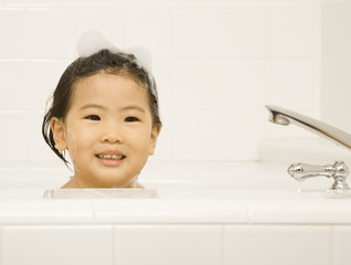 Young Asian girl smiling in bubble bath