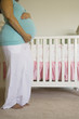 Pregnant woman standing next to crib