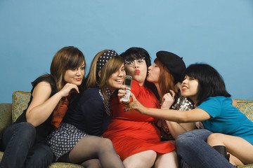 Group of young women taking self-portrait with cell phone on sofa