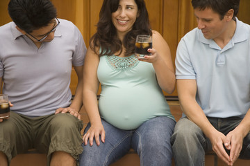 Pregnant woman sitting next to two men looking at her belly