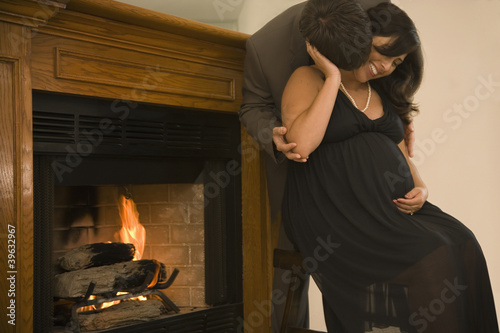 Pregnant couple in fancy clothing hugging next to fireplace