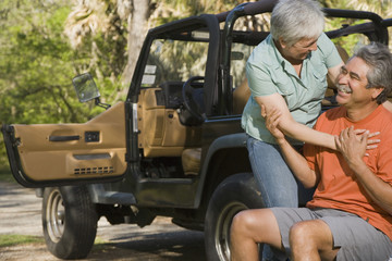 Senior Hispanic couple hugging next to jeep