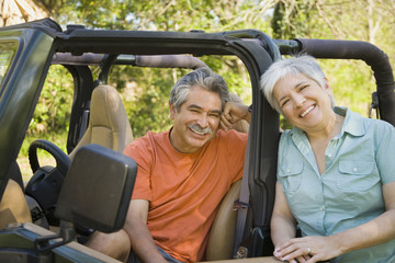 Senior Hispanic couple with jeep