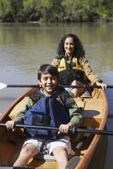 Hispanic mother and son sitting in canoe
