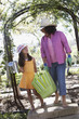 Mother and daughter carrying gardening supplies outdoors