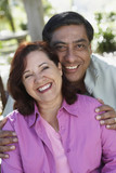 Middle-aged Hispanic couple hugging and smiling outdoors