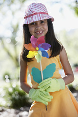 Hispanic girl holding flower pinwheel outdoors