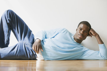 African man laying on floor leaning head on hand