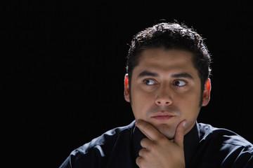 Hispanic man with hand on chin