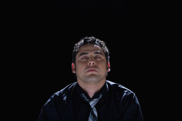 Hispanic businessman with eyes closed