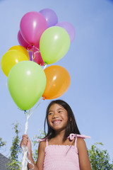 Asian girl holding bunch of balloons