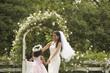 Hispanic bride and young girl dancing in circle