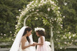 Hispanic bride and young girl smiling at each other