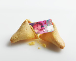 Broken fortune cookie with Swiss Franc inside