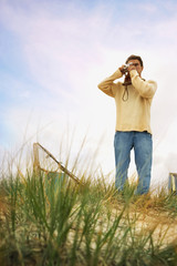 Man standing on sand dune taking photograph